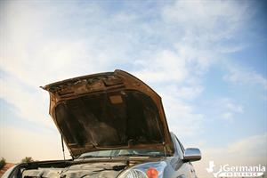 A car with an open hood exposing the engine