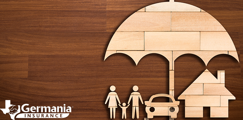 A wooden cutout depicting umbrella insurance covering a family, auto, and home