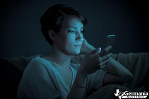 A woman bathed in blue light from her phone