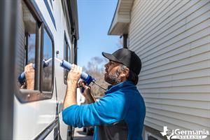 A man caulking windows, performing essential RV maintenance