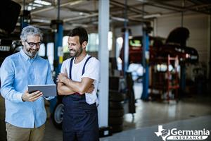 Two men in a repair shop looking at a business insurance plan on a tablet.