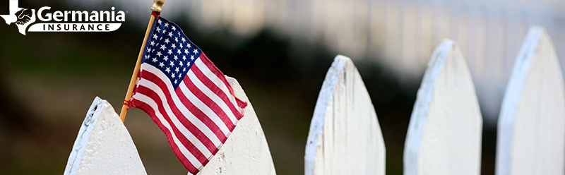 An American flag on a white fence in honor of the history of Labor Day in the USA