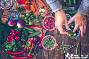 Hands placing vegetables in jars to preserve the garden harvest.