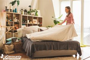 A woman making a bed, preparing her home for Airbnb guests