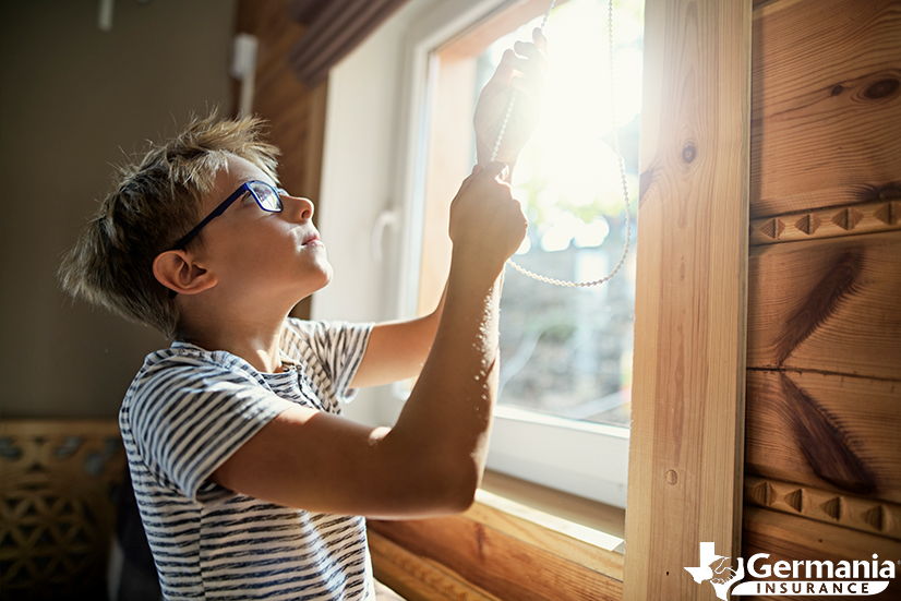 A boy drawing the blinds closed to prevent UV damage.