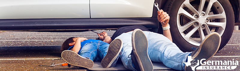 A father and child under a vehicle, performing routine auto maintenance
