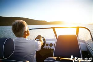 Man driving a boat on the lake, protected by boat insurance.