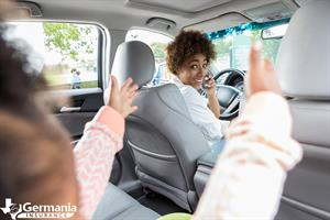 A woman talking on the phone talking to her child, common kinds of distracted driving