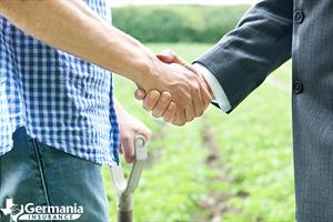 A farmer shaking hands with a farm mutual insurance company agent.