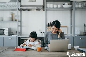 A woman working at her home business next to her daughter