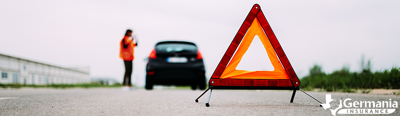 An emergency triangle behind a car that has broken down.